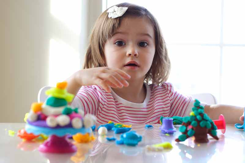 Little girl is learning to use colorful play dough in a well lit room