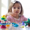 little girl learning to use colorful play dough