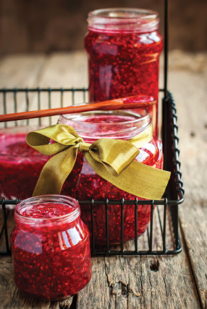 Fresh Raspberry Jam in a jars on the wooden table, close up