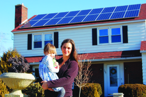Serena Graham stands outside her Waterville home with her daughter, below the solar-electric system she had installed in the fall of 2015. The system is designed to generate enough power over the course of a year to offset the home's electric demand. Getting to net zero, she said, has always been her goal.