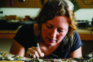 At work in her studio in Ellsworth, Nisa Smiley incorporates shells, feathers and other organic forms that wash up with the sea into her work.
